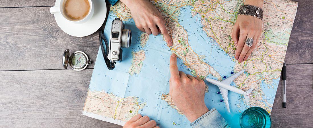 Rseplaner med karta och händer som pekar ut destinationer i Italien. Tillhörande motiv är ett leksaksflygplan, kaffekopp, kamera, penna och ett glas vatten