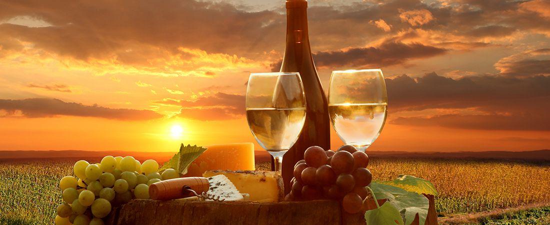 Solnedgång äver grönskande fält med en flaska vin tillhärande med druvor och ostar för två.
