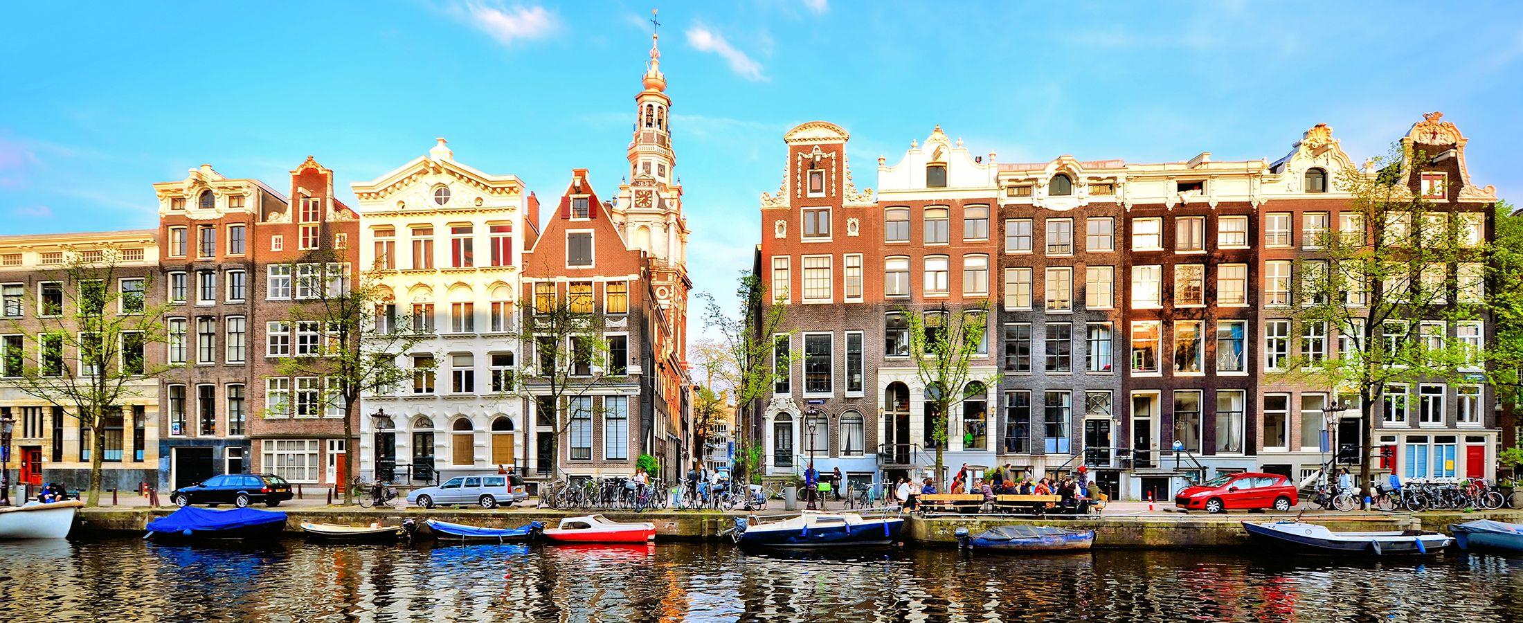 färgade hus vid vattnet med båtar intill kanalen på en resa till Amsterdam
