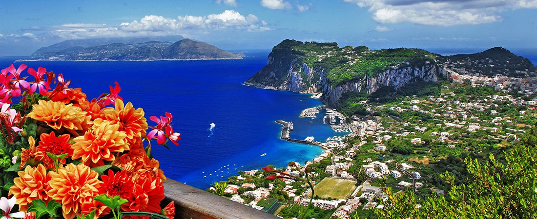 Vacker vy över staden Capri med böljande blått hav, blomster och grönskande berg