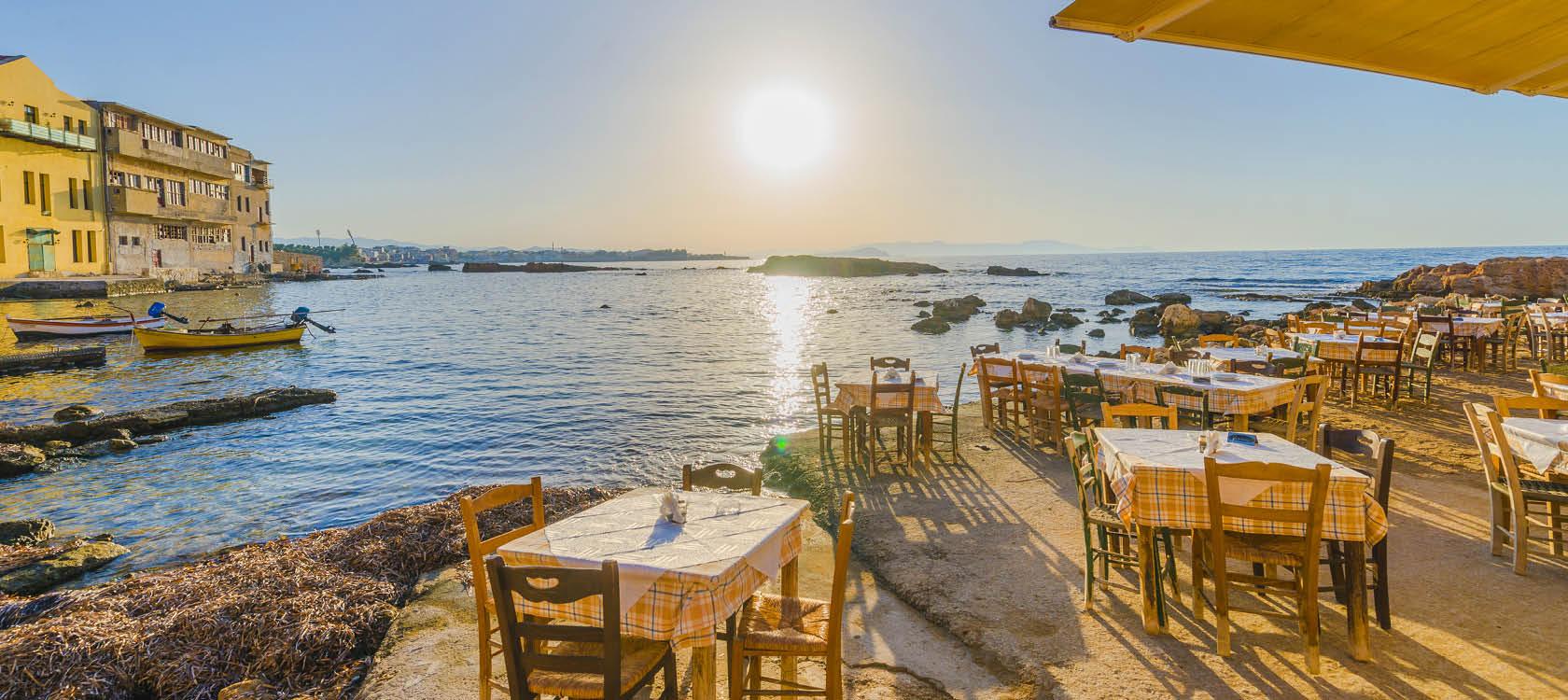Uteservering vid havet i solnedgången i Grekland.