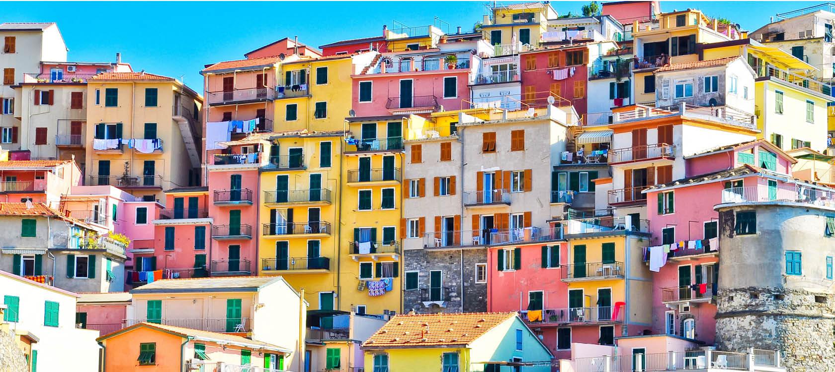 Pastellfärgade hus utmed klippväggen i Cinque Terre, Italien.
