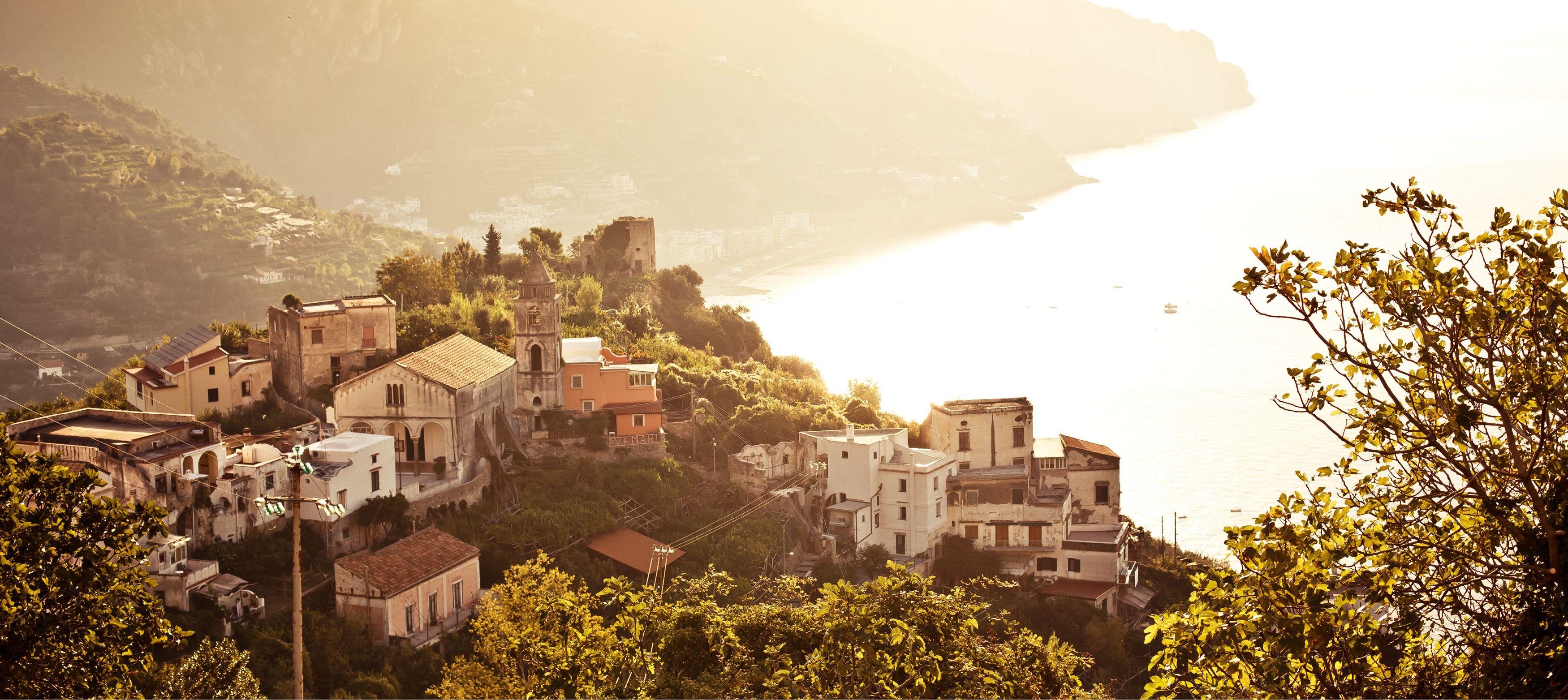 amalfikusten i solljus med idylliska hus på en kulle