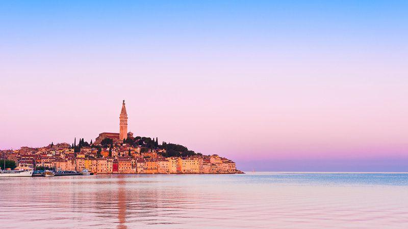 rovinj vid vattnet under en rosa himmel, kroatien
