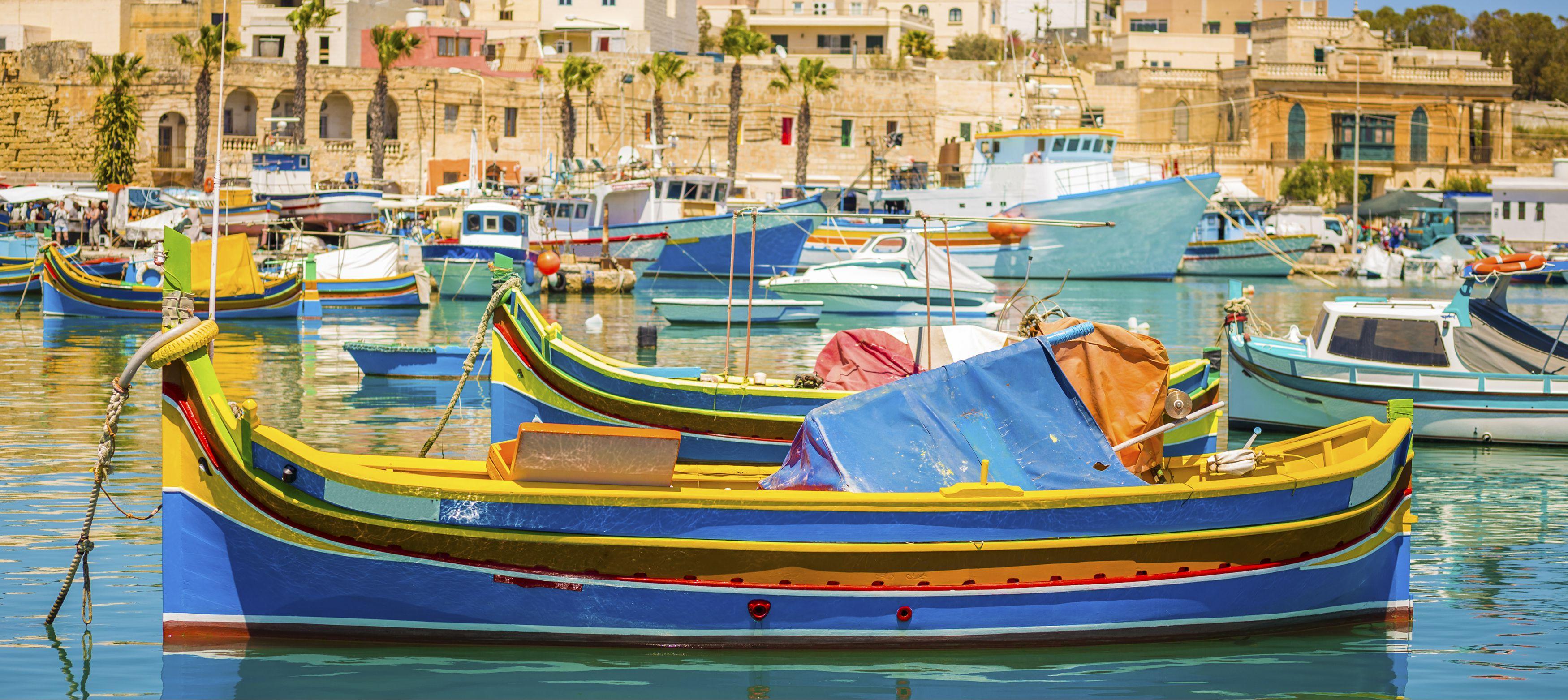 färgglada fiskebåtar intill hamnen vid palmer, malta