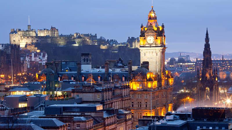 Vackra Edinburgh stad i kvällsljuset med Edinburgh Castle upplyst.