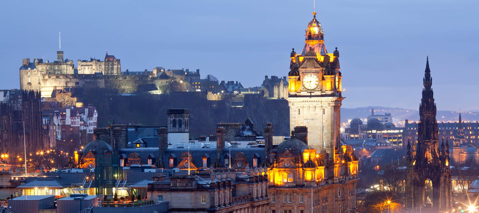 Edinburgh i kvällsljus med upplyst klocktorn på en resa till Skottland.