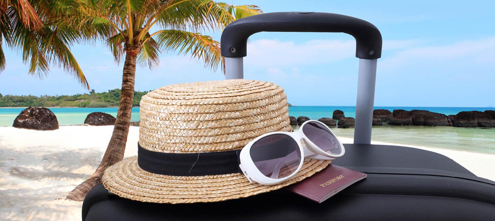 solhatt, solglasögon, pass och resväska på semestern.
