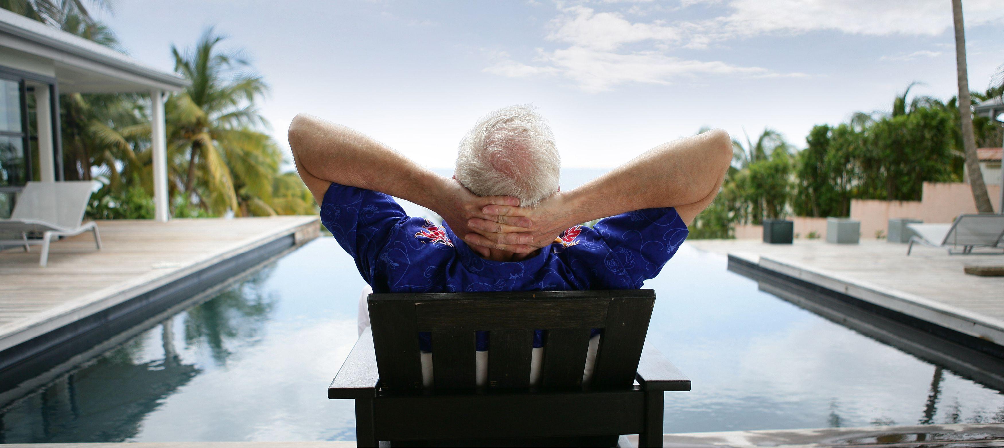 man som slappnar av vid poolen bland palmer på semestern