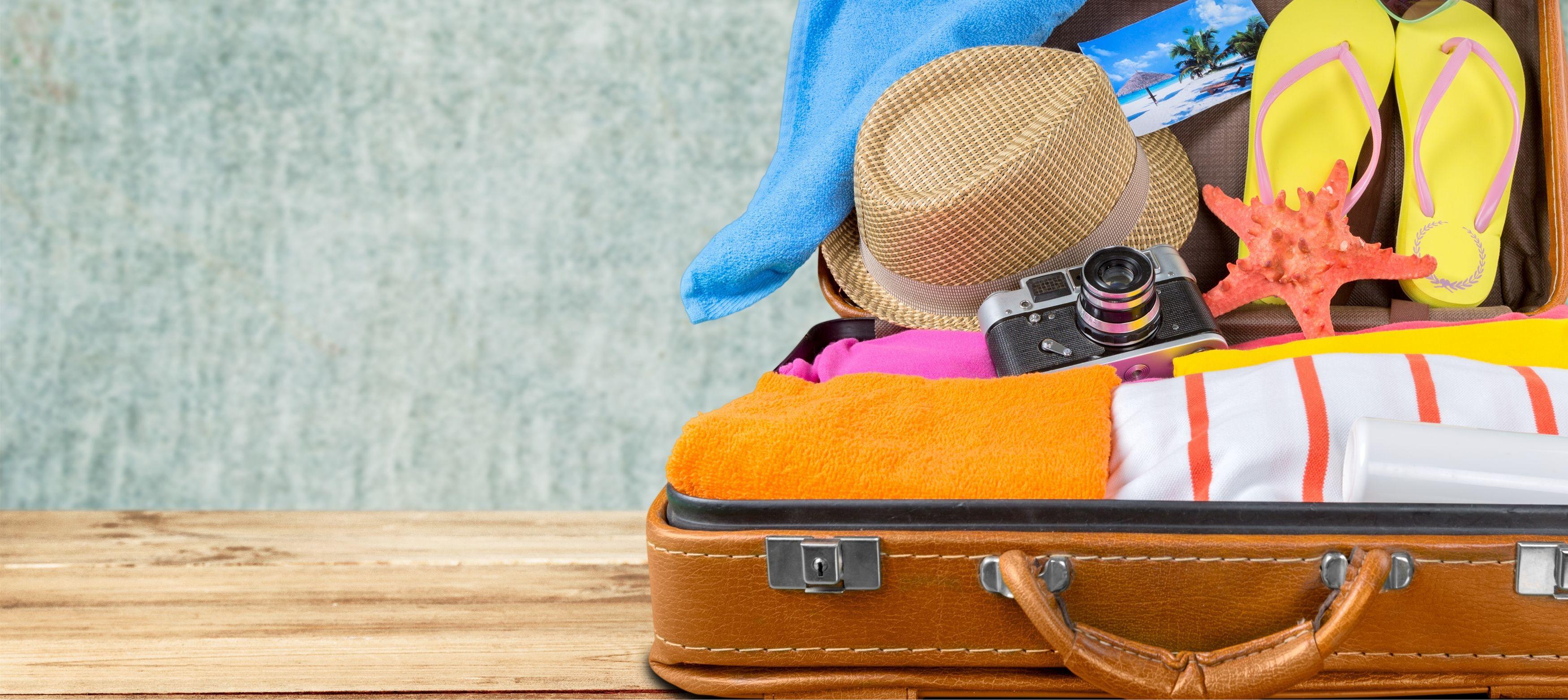 resväska med reseprylar som solhatt, flipflops, kamera och vykort