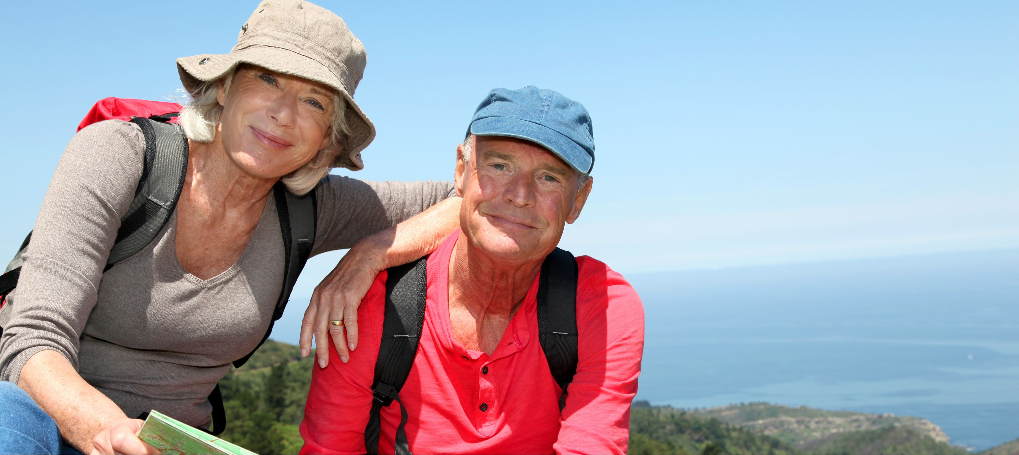 seniorpar som vandrar med karta bland vacker natur i europa