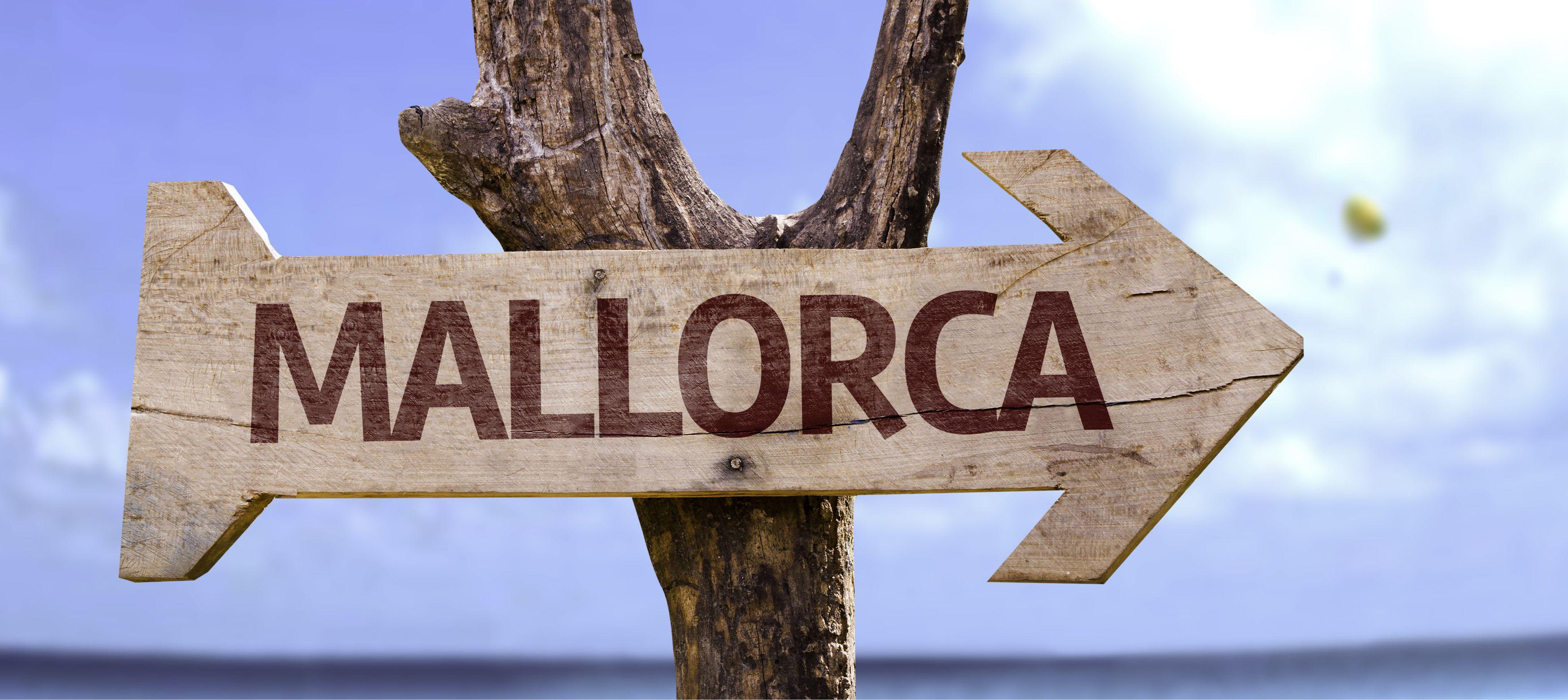 träskylt vid havet med texten mallorca