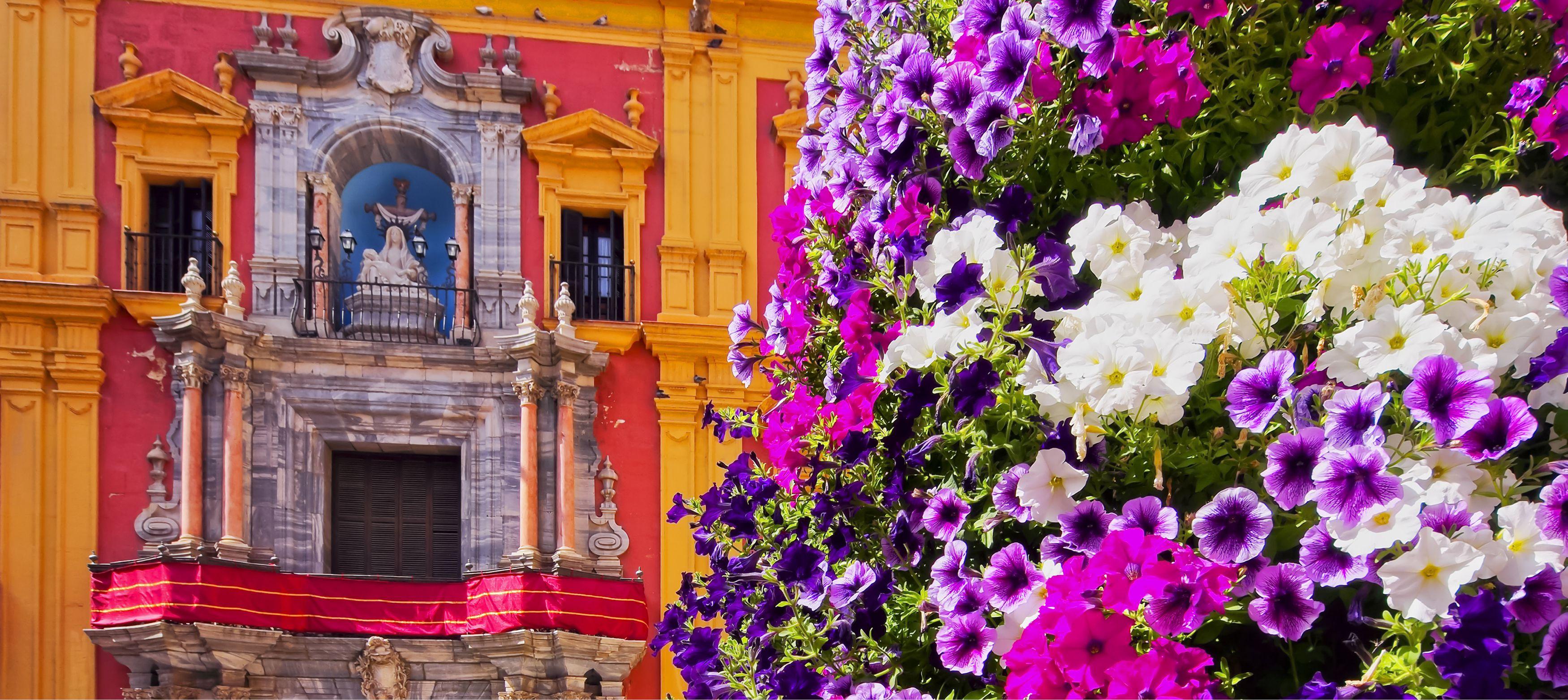 lilla och rosa blommor framför vacker byggnad i spanien