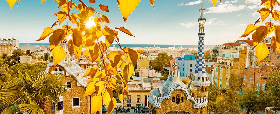 Utsikt genom gula löv över park Guell i Barcelona