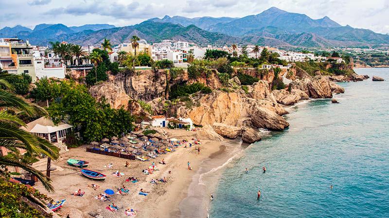 Strand i Nerja med bergen som bakgrund i Spanien.