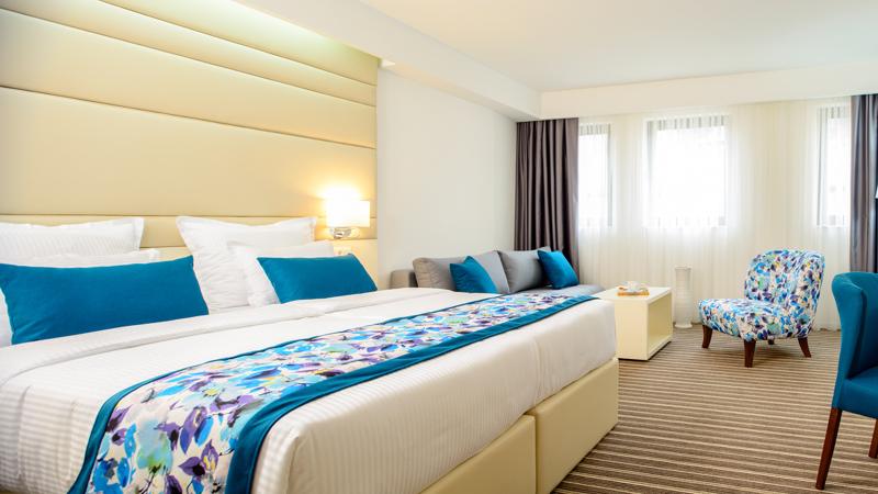 Dubbelrum med blåa inredningsdetaljer på hotell Festival på resa till Balkan.