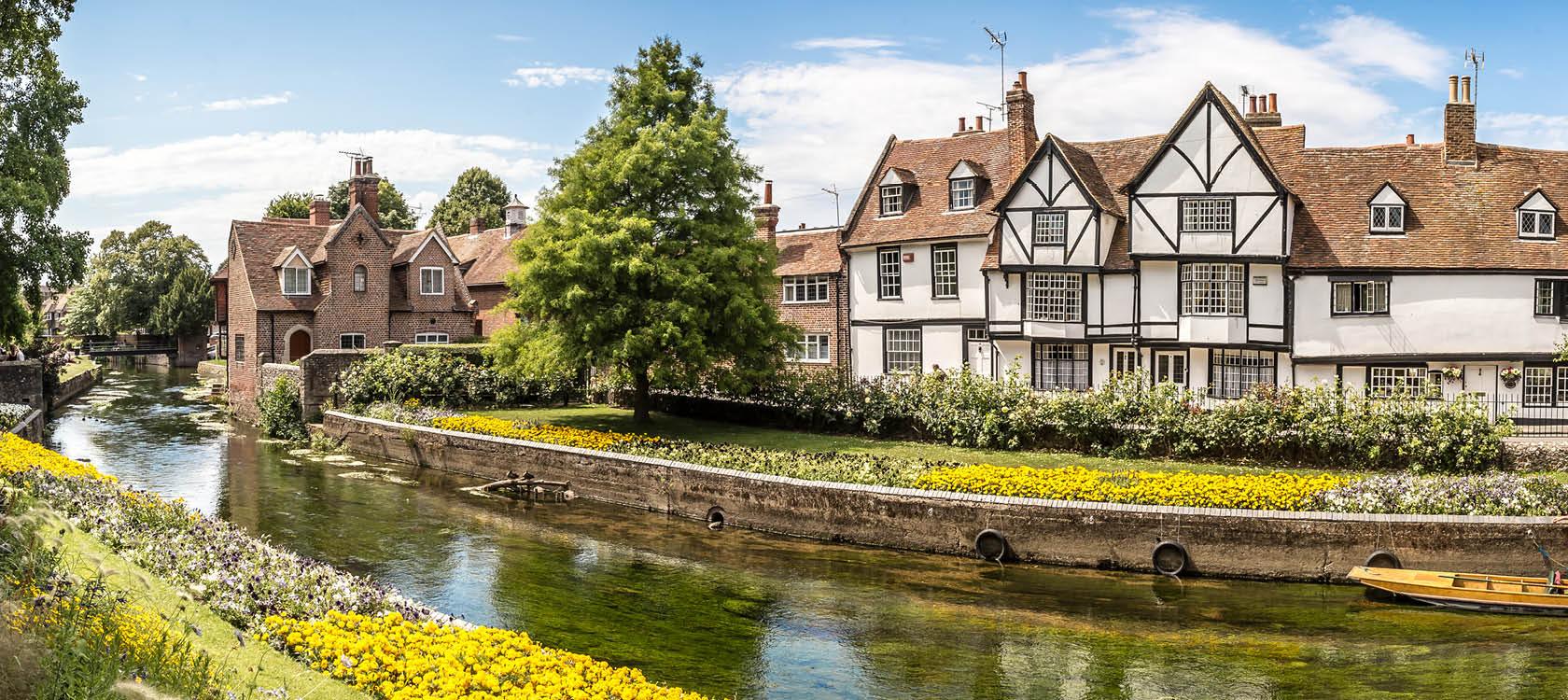 På en resa till England kan man uppleva brittisk stadsidyll med gamla hus och en bäck och blommor