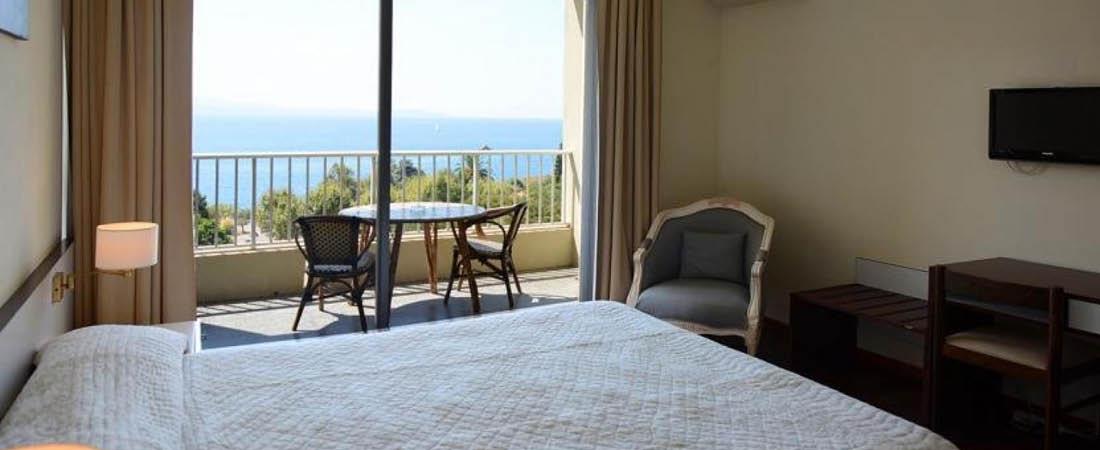 dubbelrum med säng och tv och balkong med utsikt över havet på hotell albion