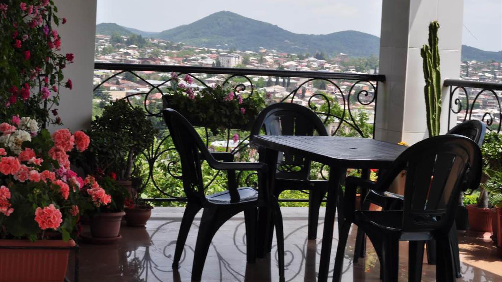 Terrass med utsikt över samhälle och bergen med vackra blommor på hotell Argo Palace Guesthouse i Kutaisis centrum, Georgien.