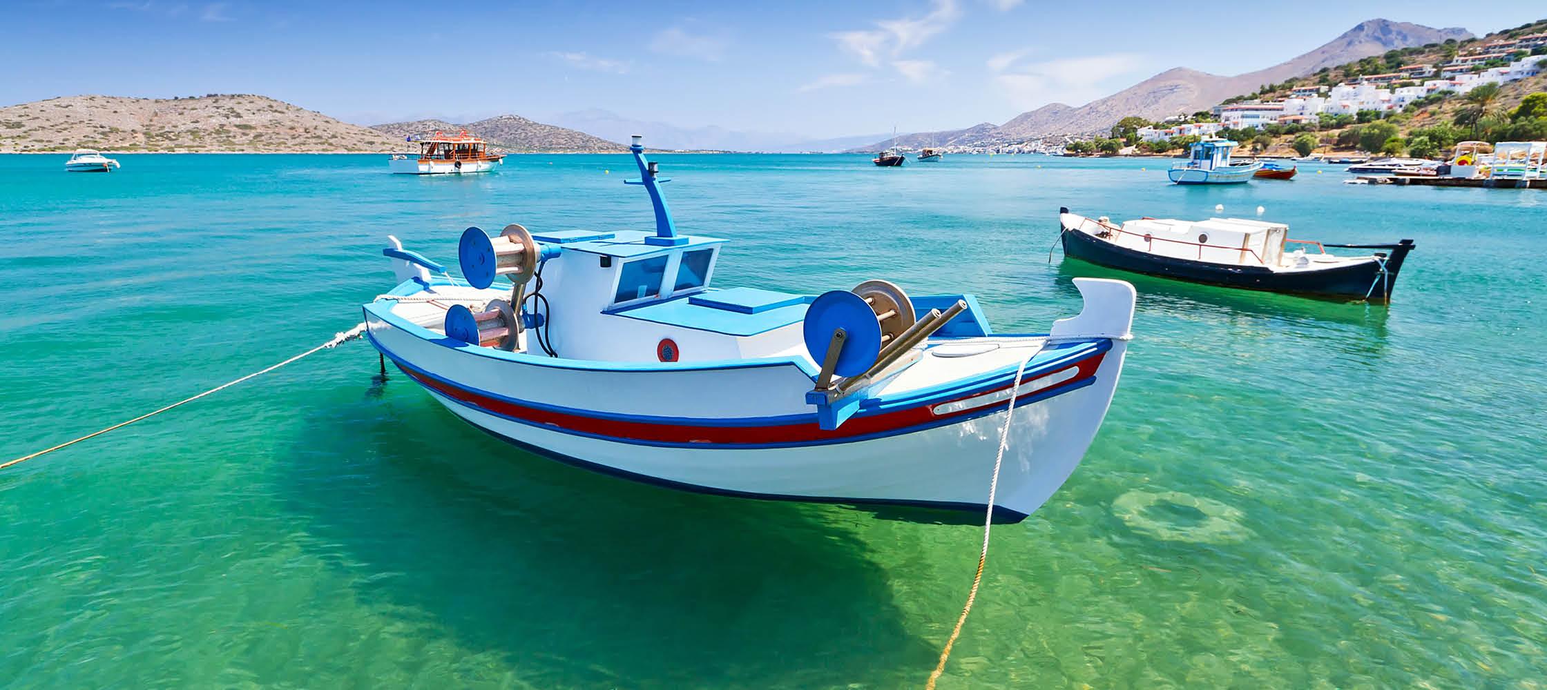 små fiskebåtar på klart hav i grekland