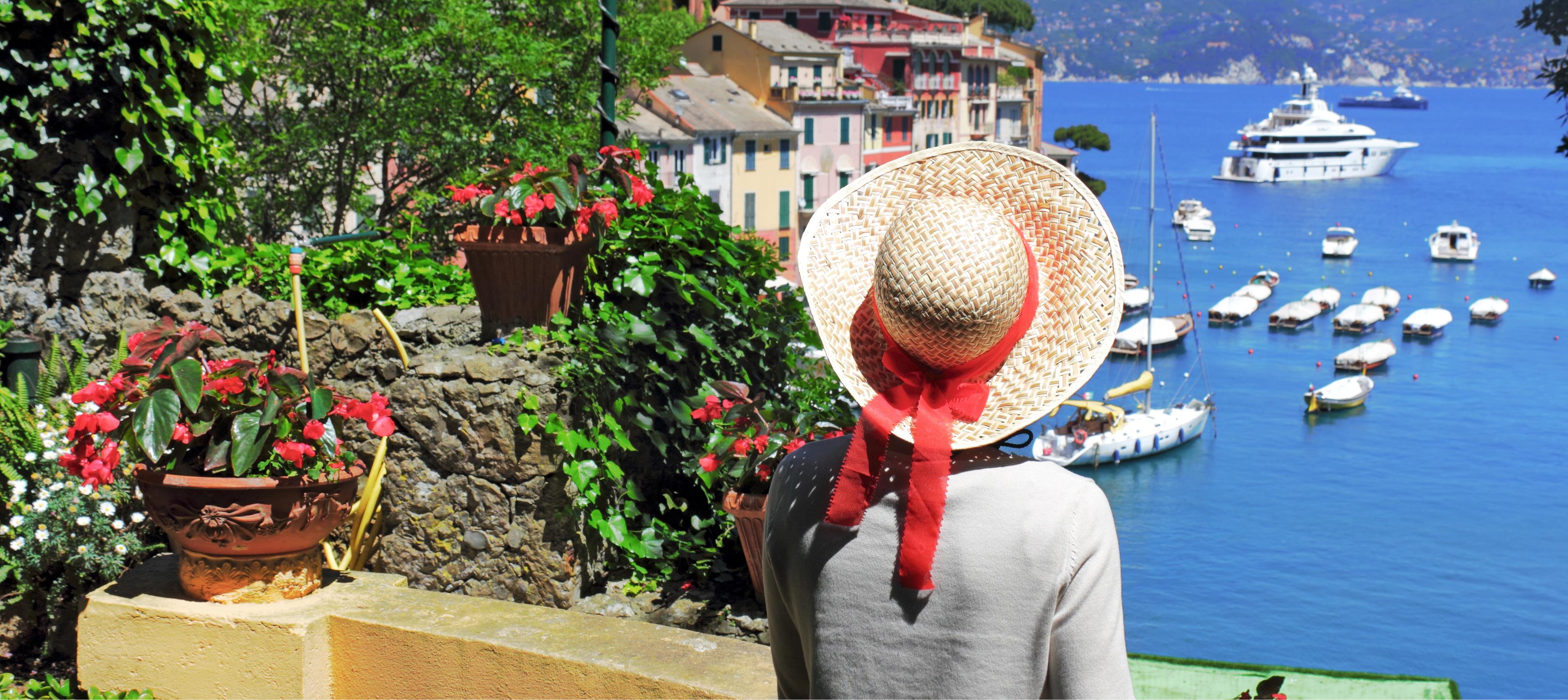 dam med hatt som tittar ut över hamnen i portofino