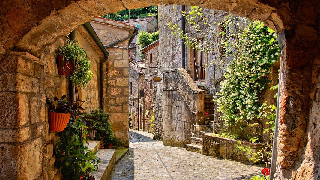 Stenport i en medeltida stad i Toscana