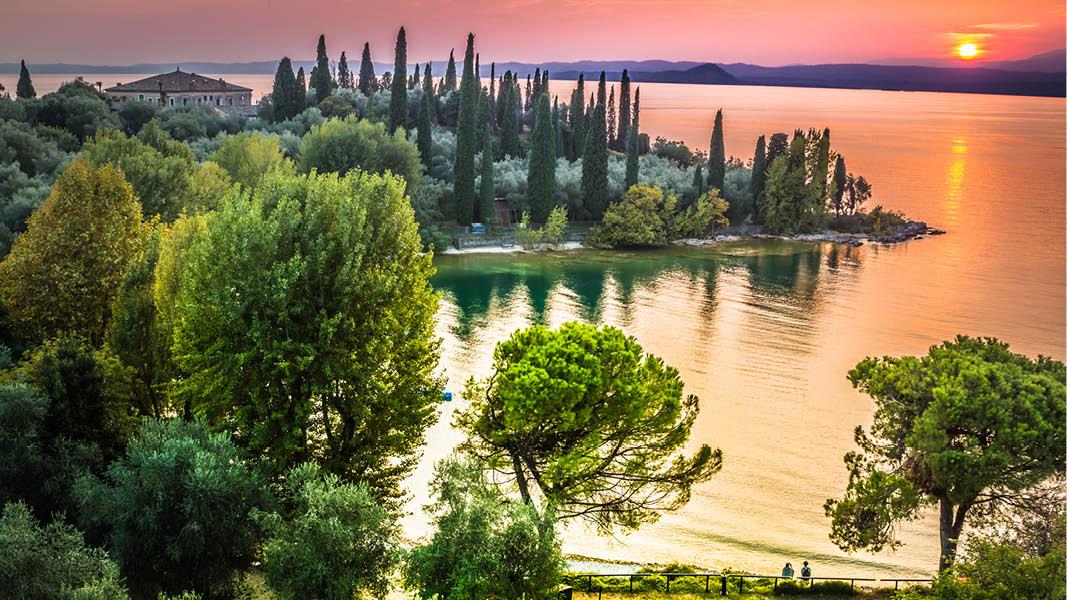 Solnedgång över landskapet och vattnet vid Gardasjön