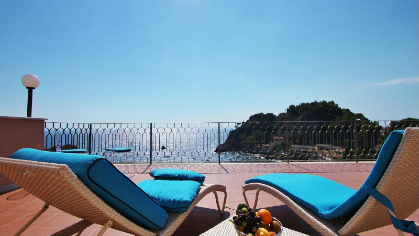 Solstolar med fruktfat på en terrass med utsikt över havet på hotell Baia Azzurra nedanför Taormina, Sicilien.