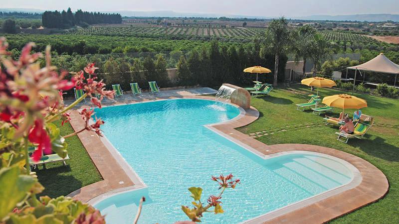 Stor utomhuspool i gröna miljöer vid hotell Il Podere på Sicilien.