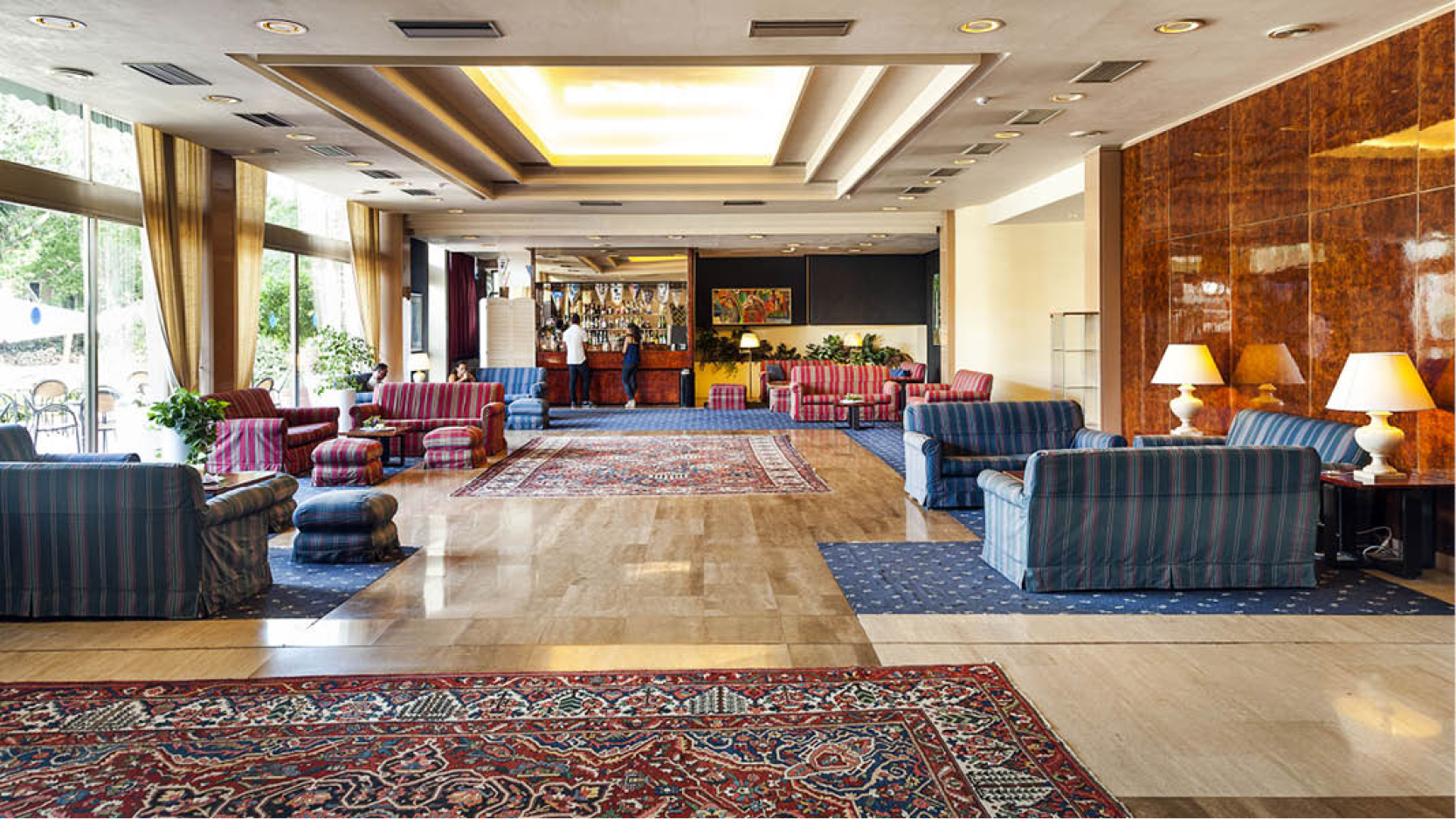 Soffgrupper med mysig belysning och bar på hotell Mondello Palace i kuststaden Mondello på den italienska ön Sicilien.