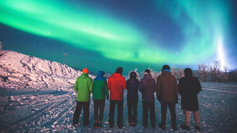 Resenärer upplever norrsken i snön på Svalbard.