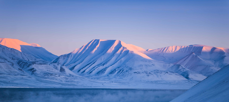 Snöklädda berg vid en sjö på Svalbard.