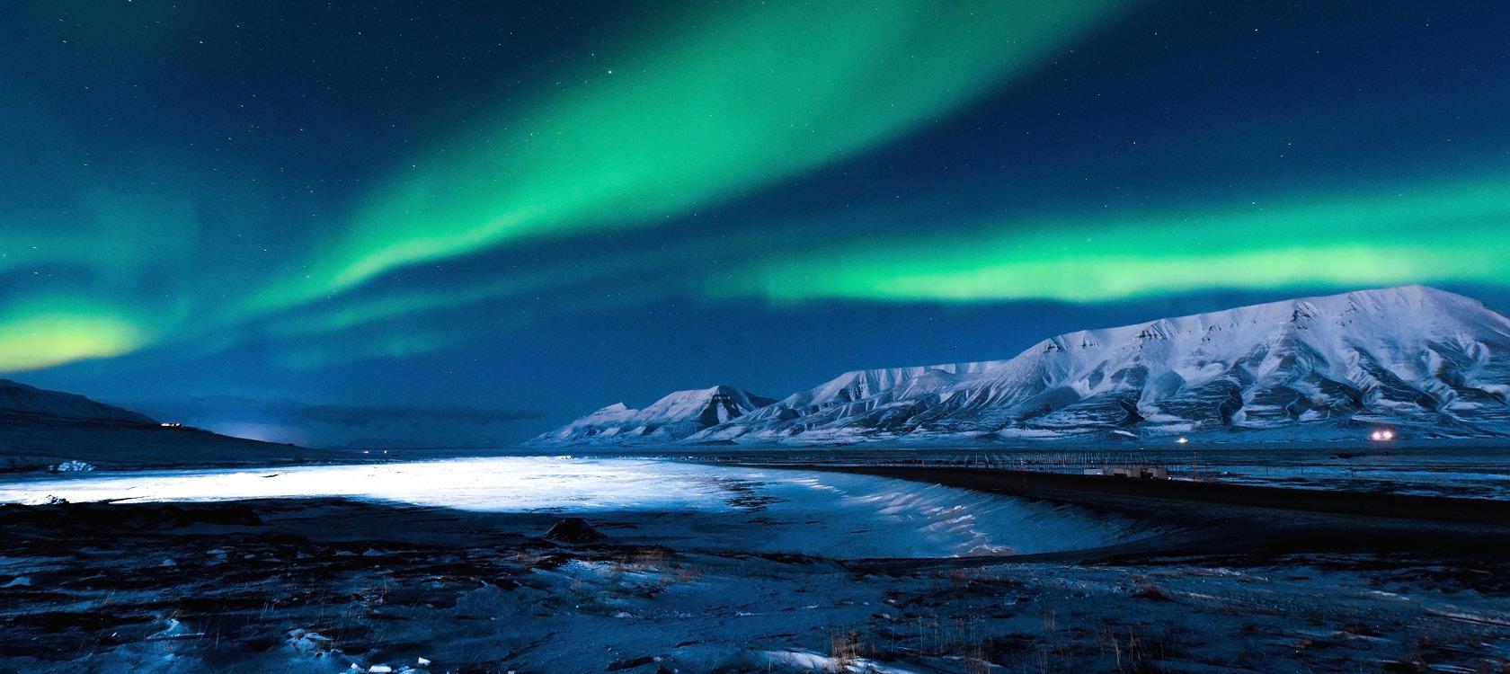 Arktisk vildmark med fjäll, glaciärer och norrsken på Svalbard.