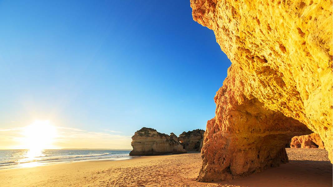Soluppgång bland havet och klippformationerna vid algarvekusten, portugal
