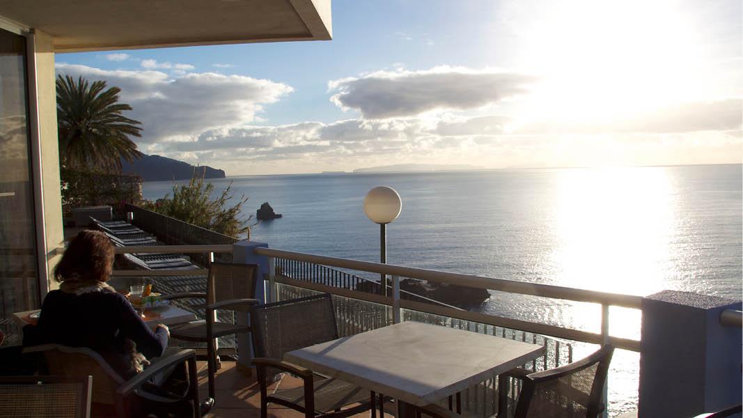 Hotellgäst blickar ut över solnedgången i horisonten på Hotel Duas Torres vid havet i Lidoområdet på Madeira.