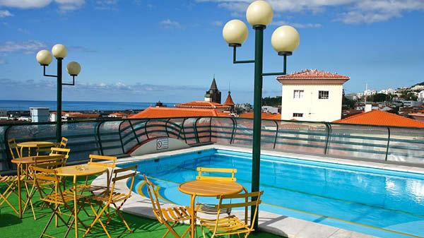 Takpool, utomhusmöbler och utsikt över havet från hotell Windsor på Madeira.