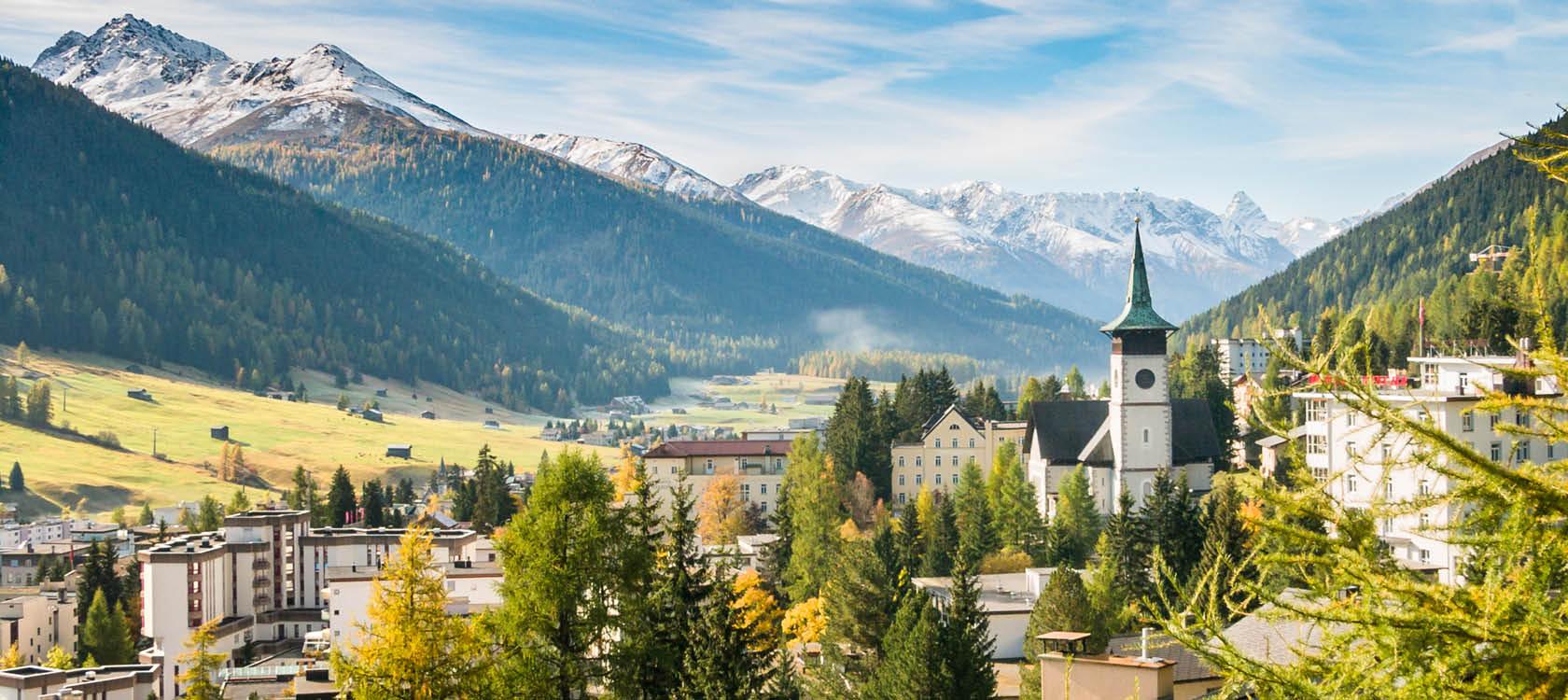 Fjällbyn Davos med grantoppar, berg och torn i Schweiz.