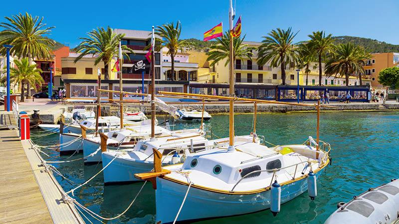 Småbåtshamn och strandpromenad i kuststad på Mallorca