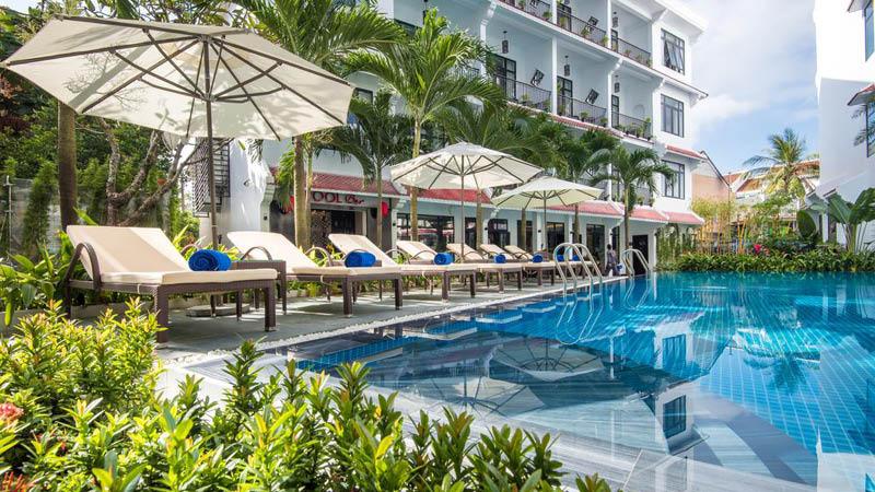 Utomhuspool med solstolar och palmer på det fyrstjärniga hotellet Belle Maison Hadana Resort and Spa i Hoi An, Vietnam.